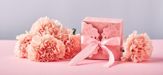 Bukiet różowych goździków i różowe pudełko upominkowe