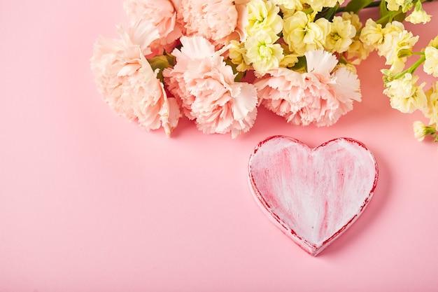 Bukiet różowych goździków i żółtej matthioli z ozdobnym sercem