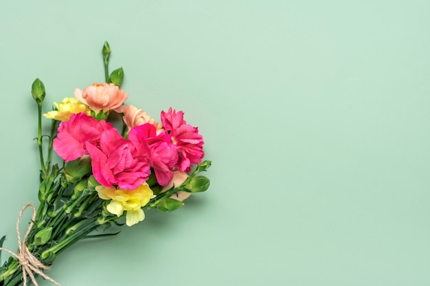 Bukiet różowych goździków na białym tle na zielonym tle widok z góry płaska świecka kartka świąteczna 8 marca