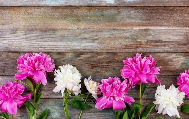 Bukiet różowych i białych kwiatów piwonii zbliżenie na drewnianym tle retro z miejscem na kopię copy