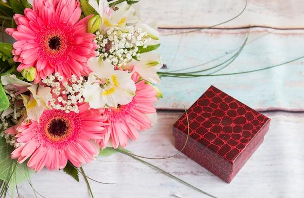Bukiet różowych kwiatów gerbery i pudełko na prezent