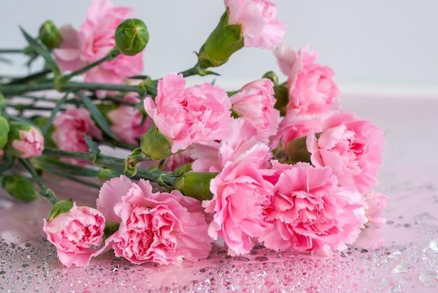 Bukiet różowych kwiatów goździka na stole z kroplami wody