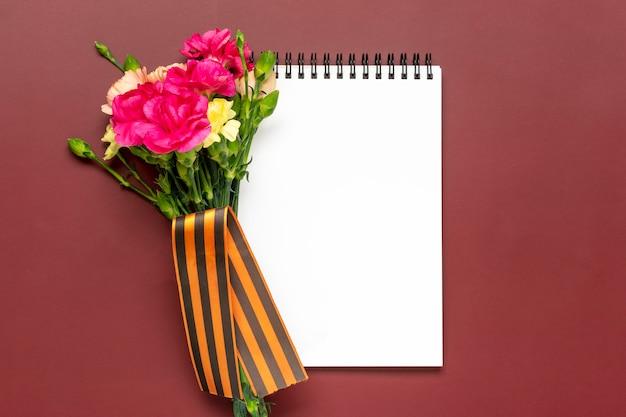 Bukiet różowych kwiatów goździków na czerwonym tle widok z góry