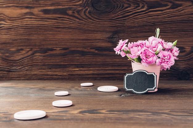 Bukiet różowych kwiatów goździków w wazonie na drewnie. puste miejsce na tekst