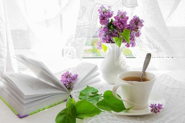 Bukiet różowych kwiatów (róż) i białego serwisu na parapecie.
