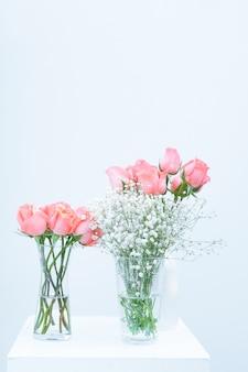 Bukiet różowych kwiatów róży eustoma w szklanym wazonie na białym tle