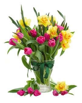 Bukiet różowych kwiatów tulipanów i żółte żonkile w szklanym wazonie na białym tle