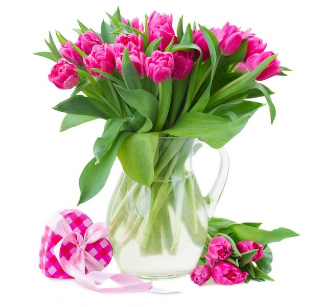 Bukiet różowych kwiatów tulipanów w szklanym wazonie na białym tle