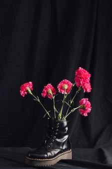 Bukiet różowych kwiatów w ciemnym bucie