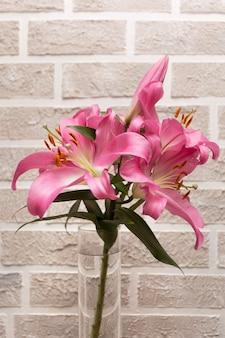 Bukiet różowych lilii w szklanym wazonie na jasnoszarym murze z cegły