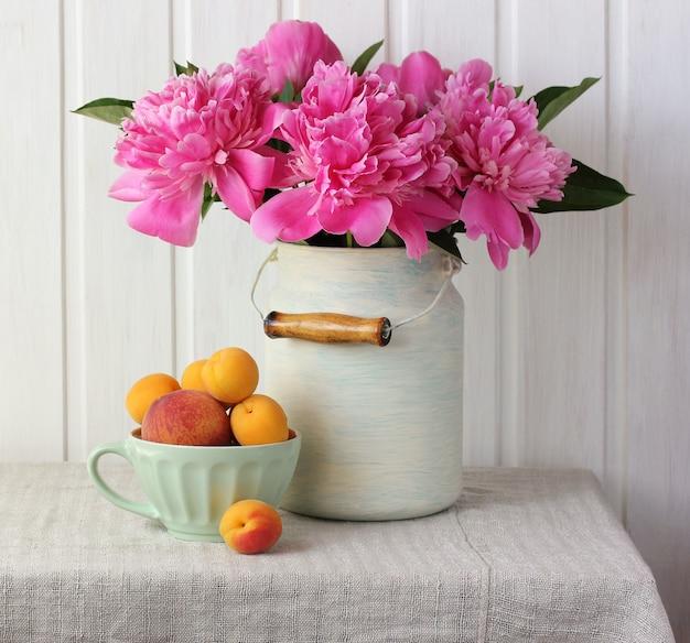 Bukiet różowych piwonii, brzoskwiń i moreli na stole.