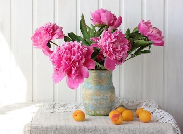 Bukiet różowych piwonii i moreli na stole.