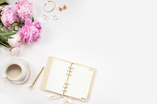 Bukiet różowych piwonii, złoty długopis, damska biżuteria i pamiętnik na białym tle. kawa w białym kubku. skopiuj miejsce.