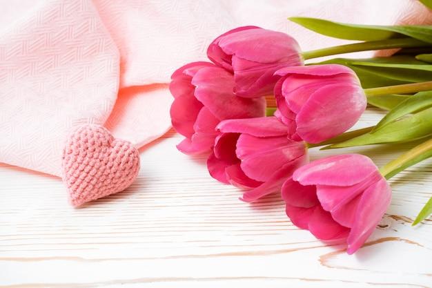 Bukiet różowych tulipanów i dzianiny serca na stole