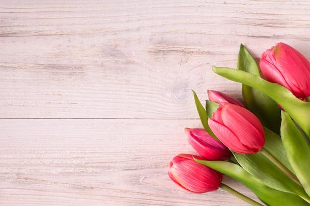 Bukiet różowych tulipanów na białym drewnianym tle