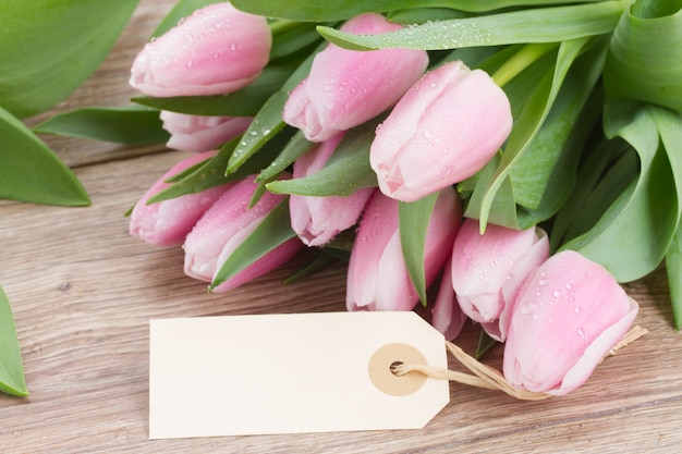 Bukiet różowych tulipanów na drewnianym stole z pustym tagiem