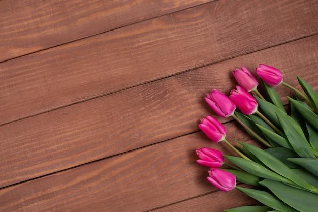 Bukiet różowych tulipanów na drewnianym