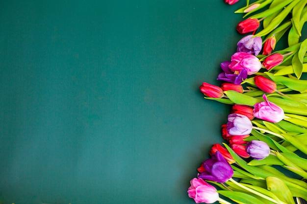 Bukiet różowych tulipanów na zielonym tle. leżał na płasko, widok z góry, miejsce na kopię. wysokiej jakości zdjęcie