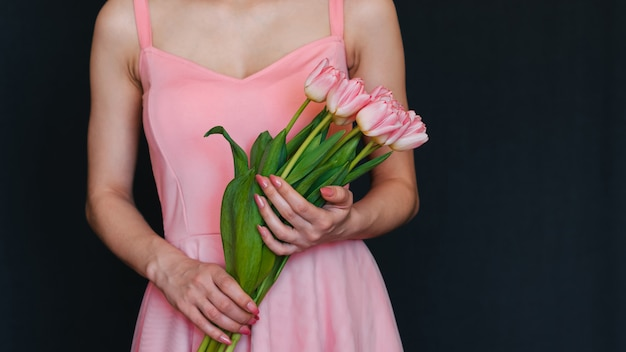 Bukiet różowych tulipanów w rękach dziewczynki