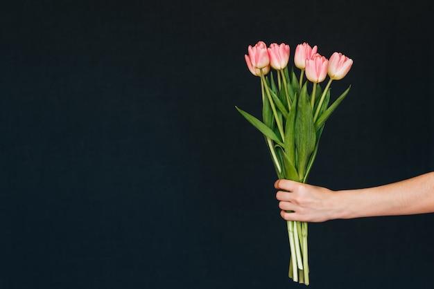 Bukiet różowych tulipanów w ręku dziewczyny
