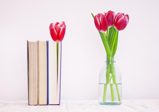 Bukiet różowych tulipanów w szklanym wazonie i książkach z kwiatową zakładką na stole