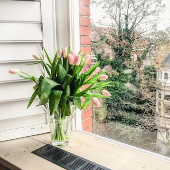 Bukiet różowych tulipanów w szklanym wazonie na oknie z otwartymi okiennicami