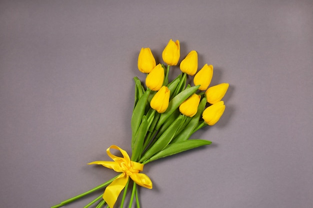 Bukiet rozświetlających żółtych tulipanów na najwyższej szarej powierzchni. wiosenne kwiaty. kolory roku 2021