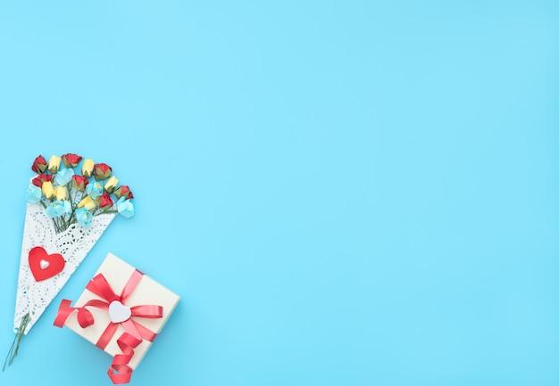 Bukiet rzemieślniczych kwiatów zawinięty w białą koronkową wiązankę i prezentowe pudełko na niebieskim tle.