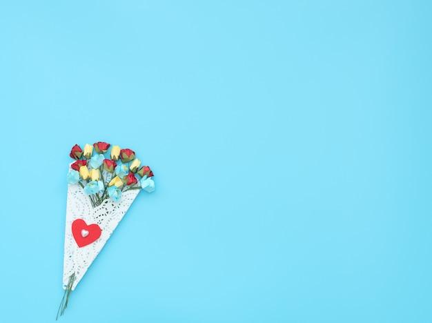 Bukiet rzemieślniczych kwiatów zawiniętych w białą koronkową wiązankę na niebieskim tle.