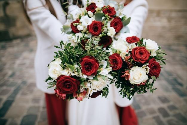 Bukiet ślubny czerwony w rękach panny młodej
