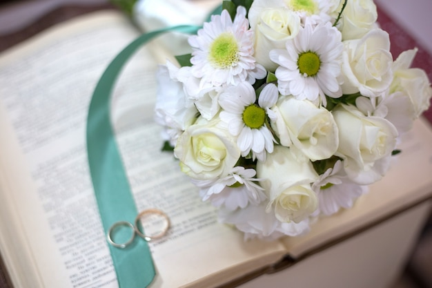 Bukiet ślubny i obrączki leżą na otwartej księdze