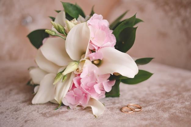 Bukiet ślubny i obrączki ślubne dla młodej pary