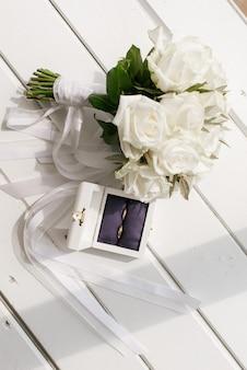 Bukiet ślubny i obrączki ślubne leżą na białym drewnianym stole, detale ślubne