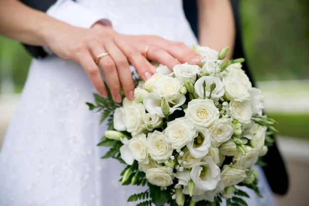 Bukiet ślubny i ręce z pierścieniami