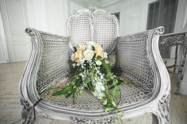 Bukiet ślubny leżący na krześle w białym studio
