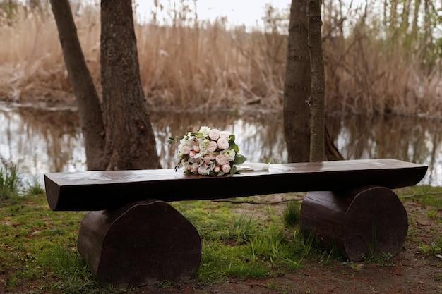 Bukiet ślubny leży na drzewie. wiosenny ślub. kwiaciarnia na ślub. państwo młodzi