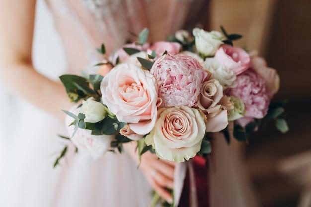 Bukiet ślubny narzeczonych z piwoniami, frezją i innymi kwiatami w rękach kobiet. jasny i liliowy wiosenny kolor. rano w pokoju