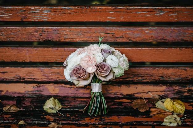 Bukiet ślubny panny młodej leży na ławce z żółtymi jesiennymi liśćmi w parku