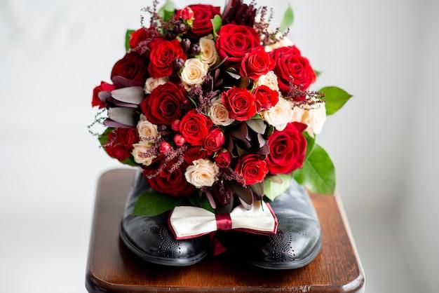 Bukiet ślubny panny młodej leży na męskich butach