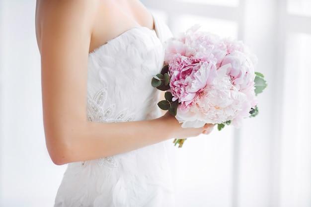 Bukiet ślubny piękne różowe kwiaty ślubne w rękach panny młodej. studio wnętrz z bliska