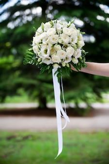 Bukiet ślubny róż w ręku panny młodej