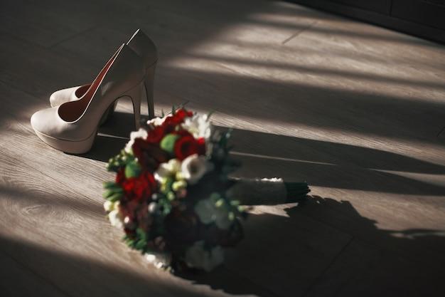 Bukiet ślubny stoi w pobliżu butów