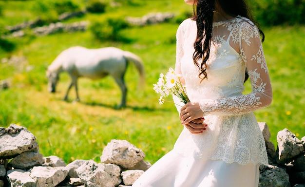 Bukiet ślubny stokrotek w rękach panny młodej