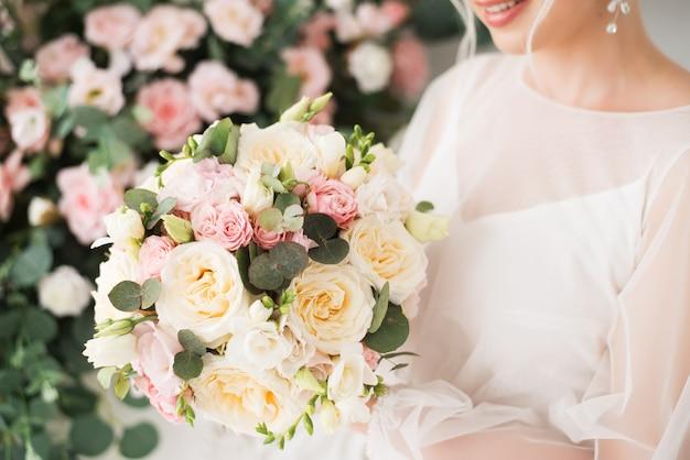 Bukiet ślubny w delikatne kwiaty w rękach panny młodej. różowe i kremowe róże