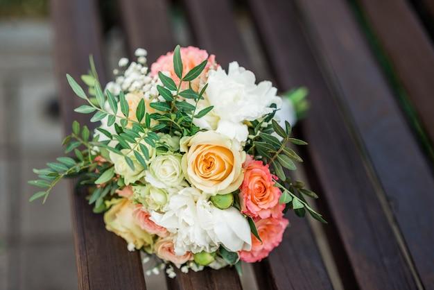 Bukiet ślubny w kolorze różowym na drewnianej ławce