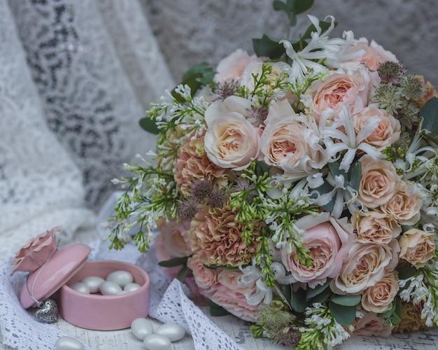 Bukiet ślubny w pastelowym kolorze, suknia ślubna i słoik z cukierkami