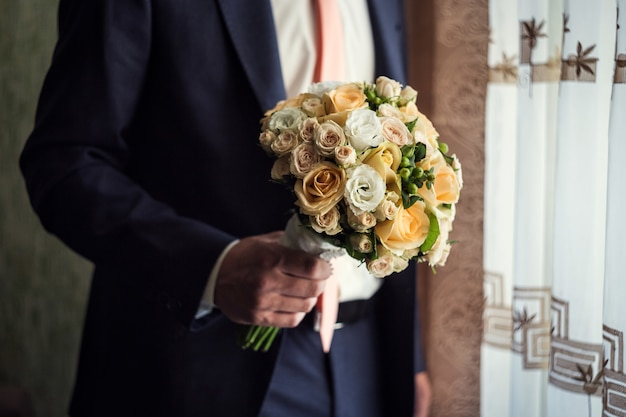 Bukiet ślubny w ręce, bukiet ślubny w ręce pana młodego, pana młodego rano, biznesmen, ślub, moda męska, styl mężczyzny