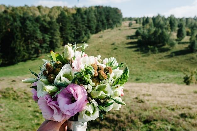 Bukiet ślubny w rękach panny młodej. widok pola, miejsce na tekst.
