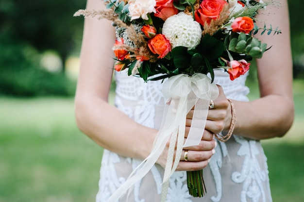 Bukiet ślubny w rękach panny młodej z czerwonymi kwiatami, różami i zielenią eukaliptusa