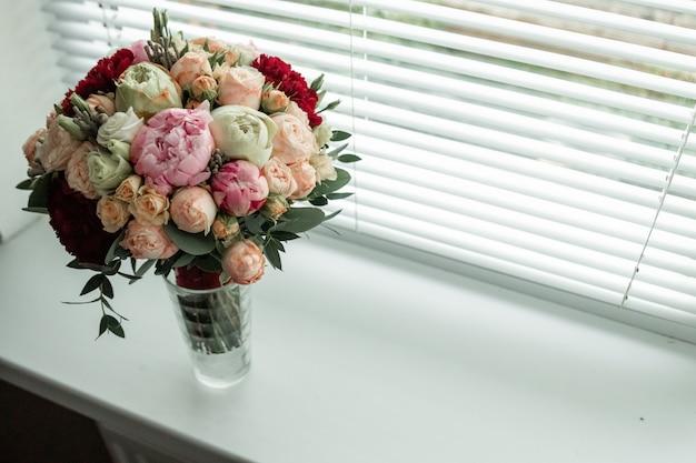 Bukiet ślubny w wazonie na oknie. małżeństwo, relacje rodzinne, akcesoria ślubne.
